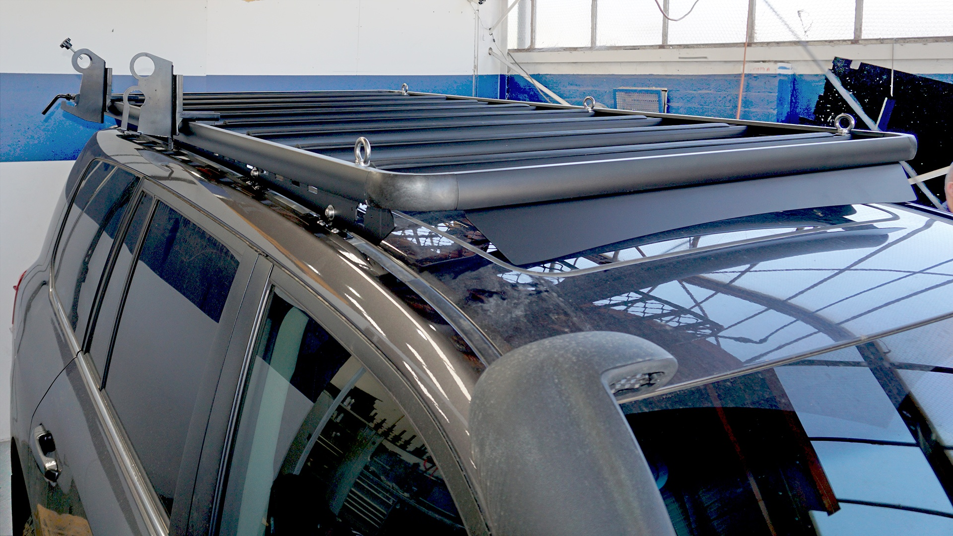 Front view of a Toyota LandCruiser 200 Series with a Wedgetail roof rack installed and a hi-lift jack and shovel holder installed as well as five tie-down eyelets.