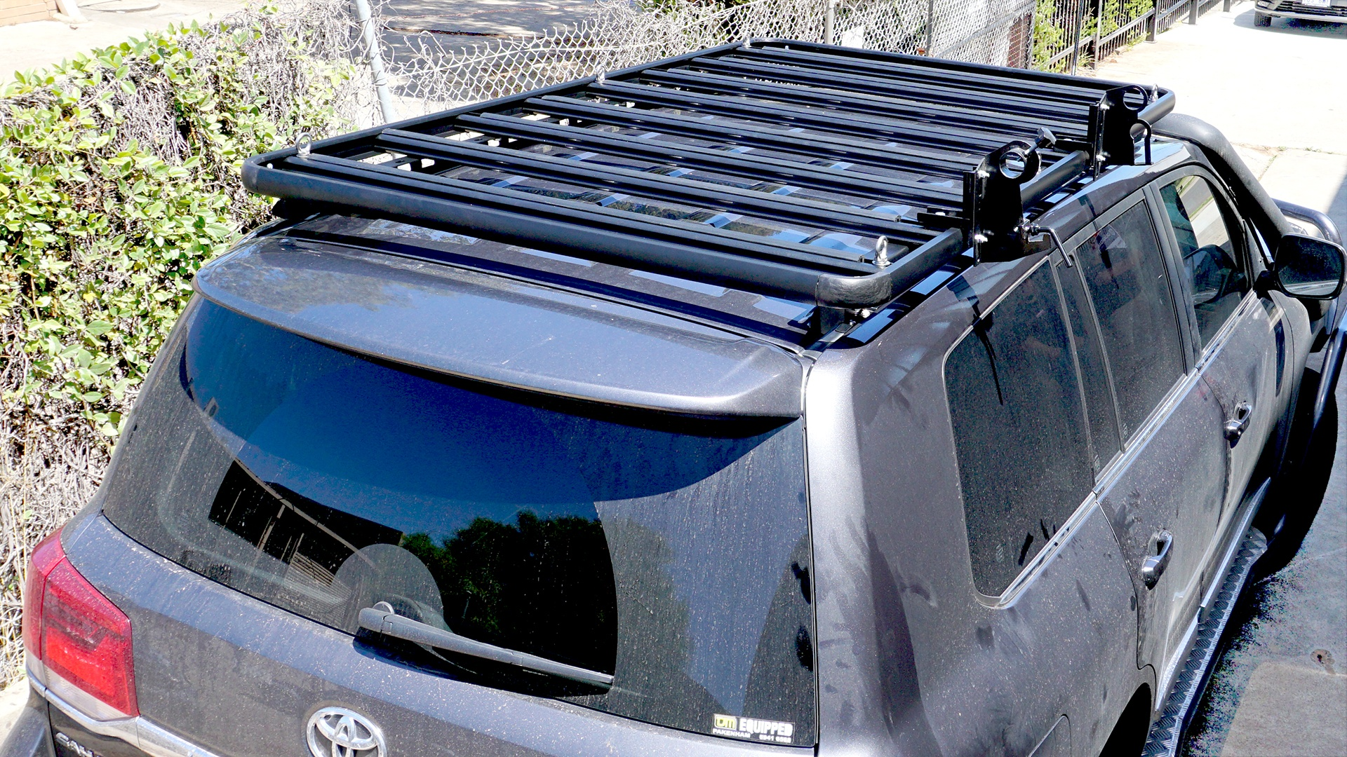 Top rear view of a Toyota LandCruiser 200 Series with a Wedgetail roof rack installed and a hi-lift jack and shovel holder installed as well as five tie-down eyelets.