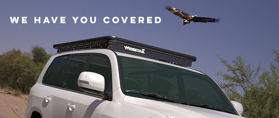 """Wedgetail roof rack on a LandCruiser 200 Series with text above it reading """"we have you covered""""."""